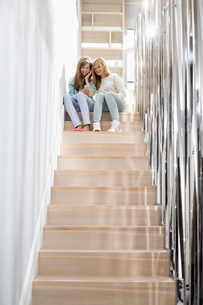 Full-length of sisters listening to music on stairwayの写真素材 [FYI03652997]