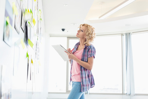 Creative businesswoman looking at papers stuck on wall while writing notes in officeの写真素材 [FYI03653010]