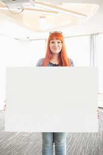 Portrait of confident businesswoman holding blank placard in creative officeの写真素材 [FYI03653042]