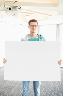 Portrait of confident businessman holding blank board in creative officeの写真素材 [FYI03653043]