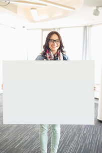 Portrait of happy businesswoman holding blank sign in creative officeの写真素材 [FYI03653046]