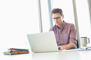 Mid-adult businessman working laptop at desk in creative officeの写真素材 [FYI03653057]