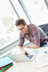 Creative businessman using laptop at desk in officeの写真素材 [FYI03653060]