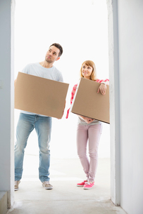 Full-length of couple with cardboard boxes standing in front of entranceの写真素材 [FYI03653077]