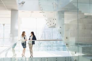 Businesswomen conversing against railing in officeの写真素材 [FYI03653115]