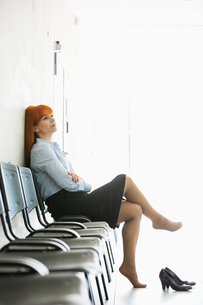 Thoughtful businesswoman sitting with legs crossed on chair in officeの写真素材 [FYI03653138]
