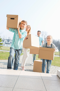 Family carrying cardboard boxes while entering new houseの写真素材 [FYI03653159]