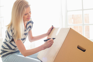 Woman labeling moving box at homeの写真素材 [FYI03653160]
