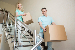 Couple carrying cardboard boxes while moving down steps at new homeの写真素材 [FYI03653161]