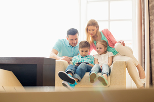 Family looking at boy playing hand-held video game at homeの写真素材 [FYI03653173]