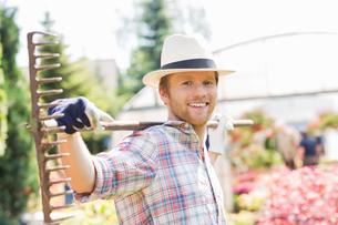 Portrait of smiling gardener carrying rake on shoulders at plant nurseryの写真素材 [FYI03653228]
