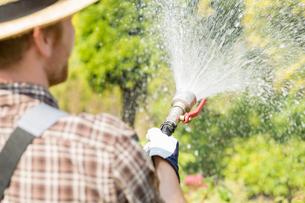 Rear view of gardener watering plants at gardenの写真素材 [FYI03653234]