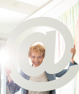 Portrait of happy businesswoman looking through at sign in creative officeの写真素材 [FYI03653240]