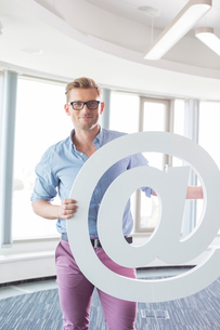 Portrait of creative businessman holding at sign in officeの写真素材 [FYI03653268]