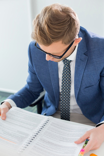 Creative businessman reading file at desk in officeの写真素材 [FYI03653281]
