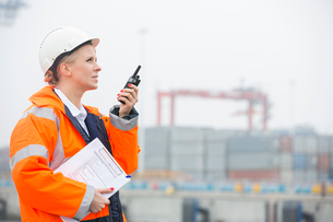 Side view of female engineer using walkie-talkie in shipping yardの写真素材 [FYI03653322]