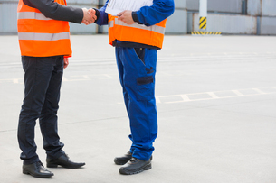 Low section of workers shaking hands in shipping yardの写真素材 [FYI03653331]