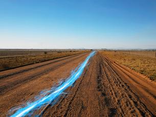Blue streak of light on dirt road against clear skyの写真素材 [FYI03653349]
