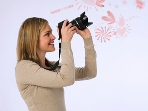 Side view of young woman photographing various patters over white backgroundの写真素材 [FYI03653350]