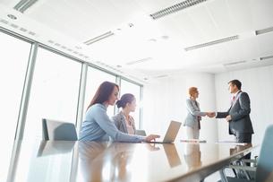 Businesspeople shaking hands in board roomの写真素材 [FYI03653371]