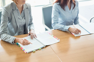 Midsection of businesswomen with books at table in officeの写真素材 [FYI03653401]