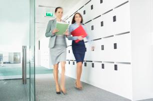 Blurred view of businesswomen walking in officeの写真素材 [FYI03653413]