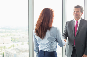 Smiling businessman shaking hands with businesswoman in officeの写真素材 [FYI03653417]