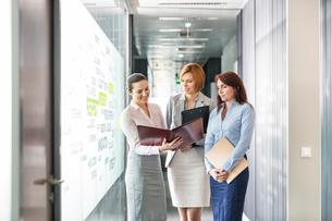 Businesswomen with file folders discussing in office corridorの写真素材 [FYI03653432]