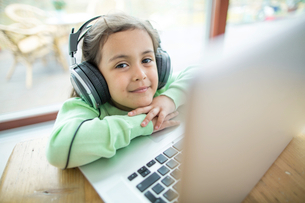Portrait of cute girl listening to music on headphones with laptop at tableの写真素材 [FYI03653483]