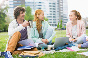 Young man having coffee while studying with female friends at college campusの写真素材 [FYI03653501]