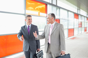 Happy middle aged businessmen talking while walking in railroad stationの写真素材 [FYI03653510]