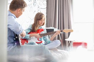 Father and daughter playing electric guitars at homeの写真素材 [FYI03653521]