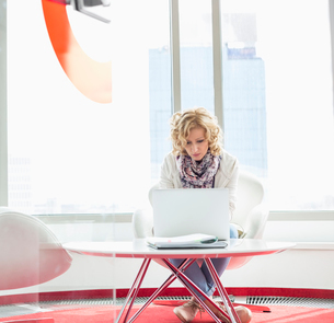 Businesswoman using laptop in creative officeの写真素材 [FYI03653538]