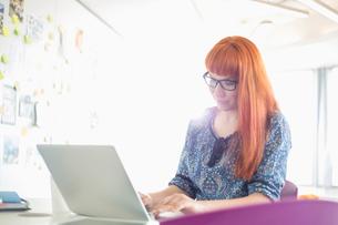 Businesswoman using laptop in creative officeの写真素材 [FYI03653541]