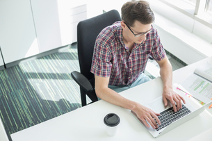 High angle view of businessman using laptop at desk in creative officeの写真素材 [FYI03653546]