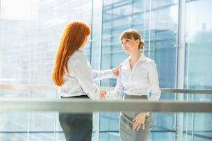 Businesswomen shaking hands in officeの写真素材 [FYI03653560]