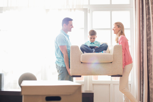 Happy parents carrying son on armchair in new houseの写真素材 [FYI03653561]