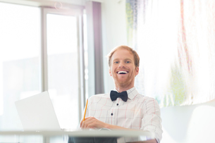 Cheerful businessman sitting at desk in creative officeの写真素材 [FYI03653582]