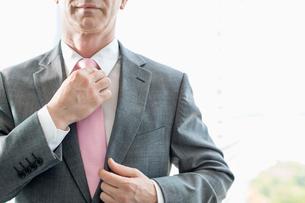 Midsection of mature businessman adjusting necktieの写真素材 [FYI03653603]