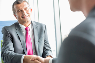 Smiling mature businessman shaking hands with partner in officeの写真素材 [FYI03653606]