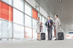 Full length of businesspeople with luggage talking on railroad platformの写真素材 [FYI03653616]