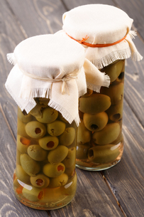 Pickled olives in jar on wooden tableの写真素材 [FYI03653698]