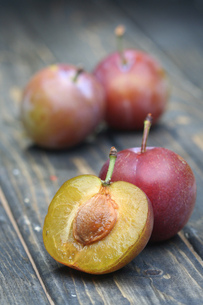 Plums on wooden table - close-upの写真素材 [FYI03654064]