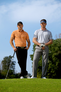 Portrait of young men standing with golf sticks on golf courseの写真素材 [FYI03654218]