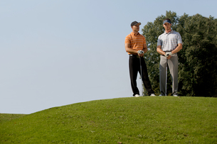 Portrait of young men standing with golf sticks on golf courseの写真素材 [FYI03654220]