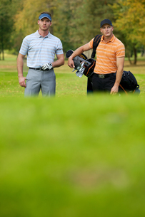 Young men standing on golf course carrying bagsの写真素材 [FYI03654239]