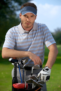 Portrait of young man standing by golf bag full of sticksの写真素材 [FYI03654247]