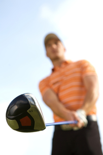 Young man playing golf, low angle viewの写真素材 [FYI03654266]
