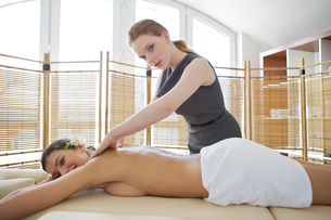 Portrait of young woman receiving massage from masseuseの写真素材 [FYI03654280]