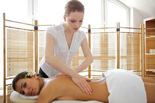 Portrait of young woman receiving massage from masseuseの写真素材 [FYI03654283]